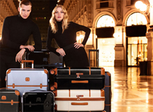 a male and a female models posing behind suitcases